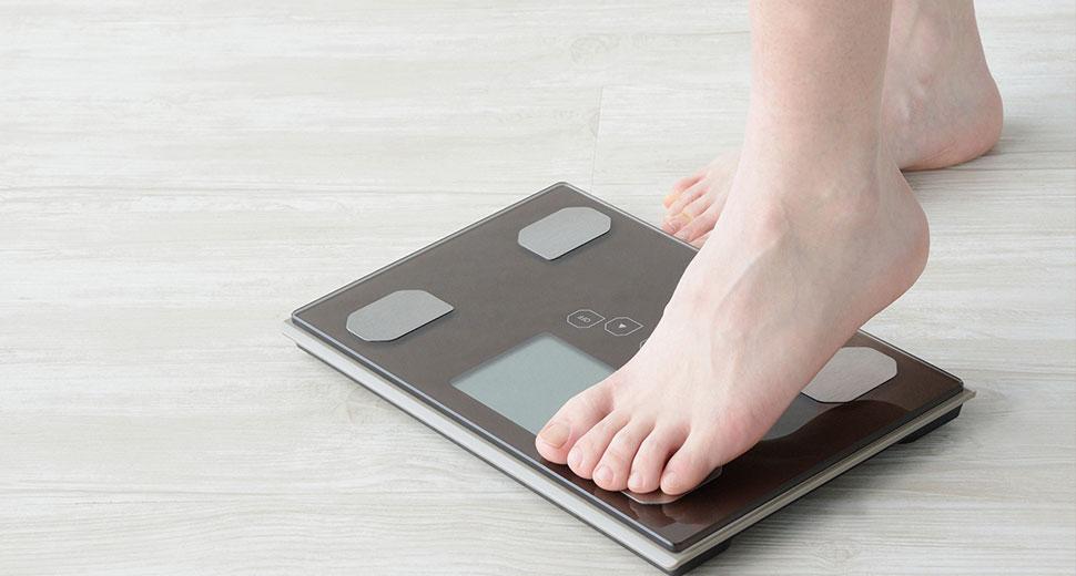 女性が体重計に乗る様子